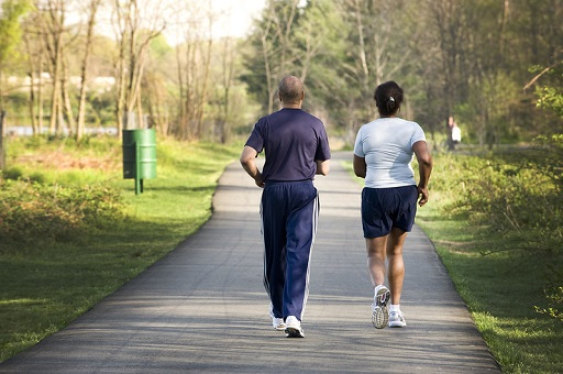 Man and woman speed walking down a trail